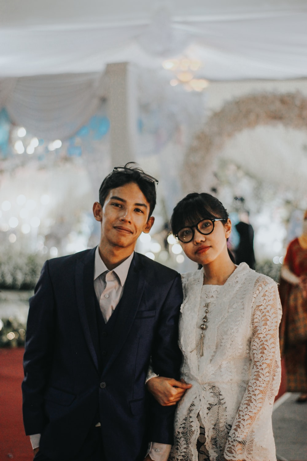 man in black suit jacket beside woman in white lace floral dress