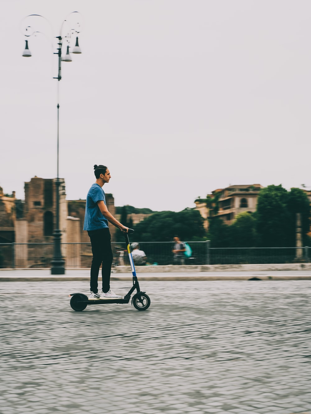 man in pink shirt and black pants riding kick scooter on water during daytime