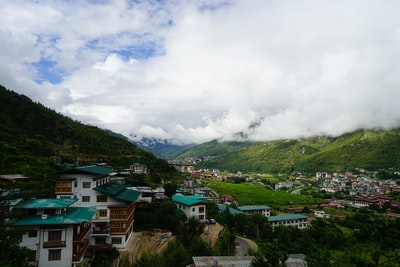 houses on green grass field under white clouds during daytime bhutan zoom background