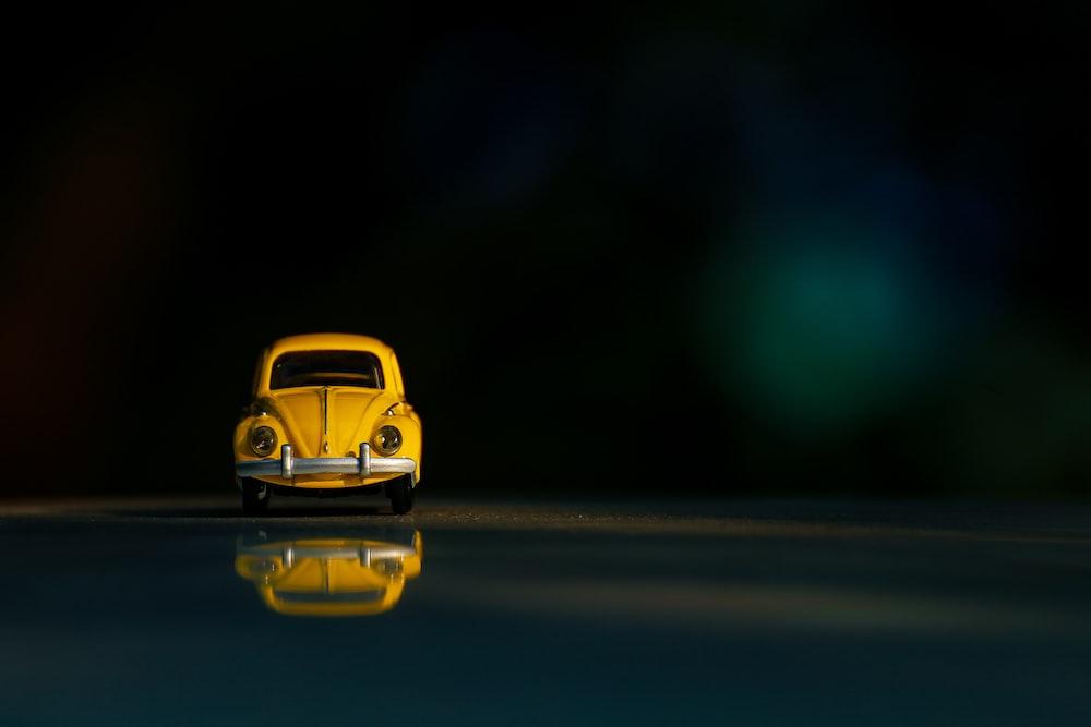 yellow car on black asphalt road