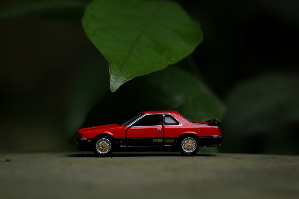 red coupe scale model on brown wooden table
