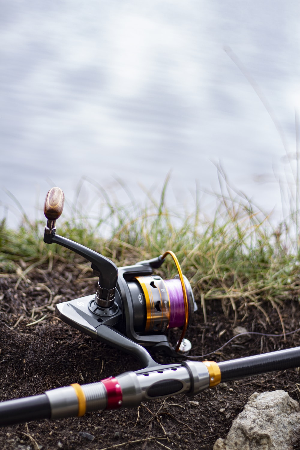 black and silver fishing reel on brown soil