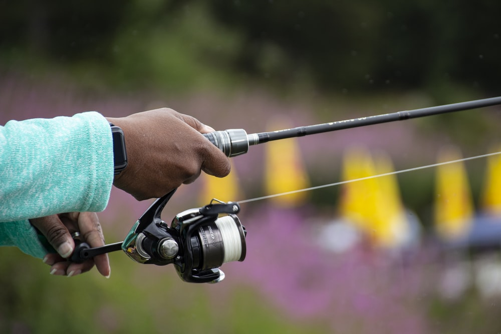 person holding black and silver fishing rod
