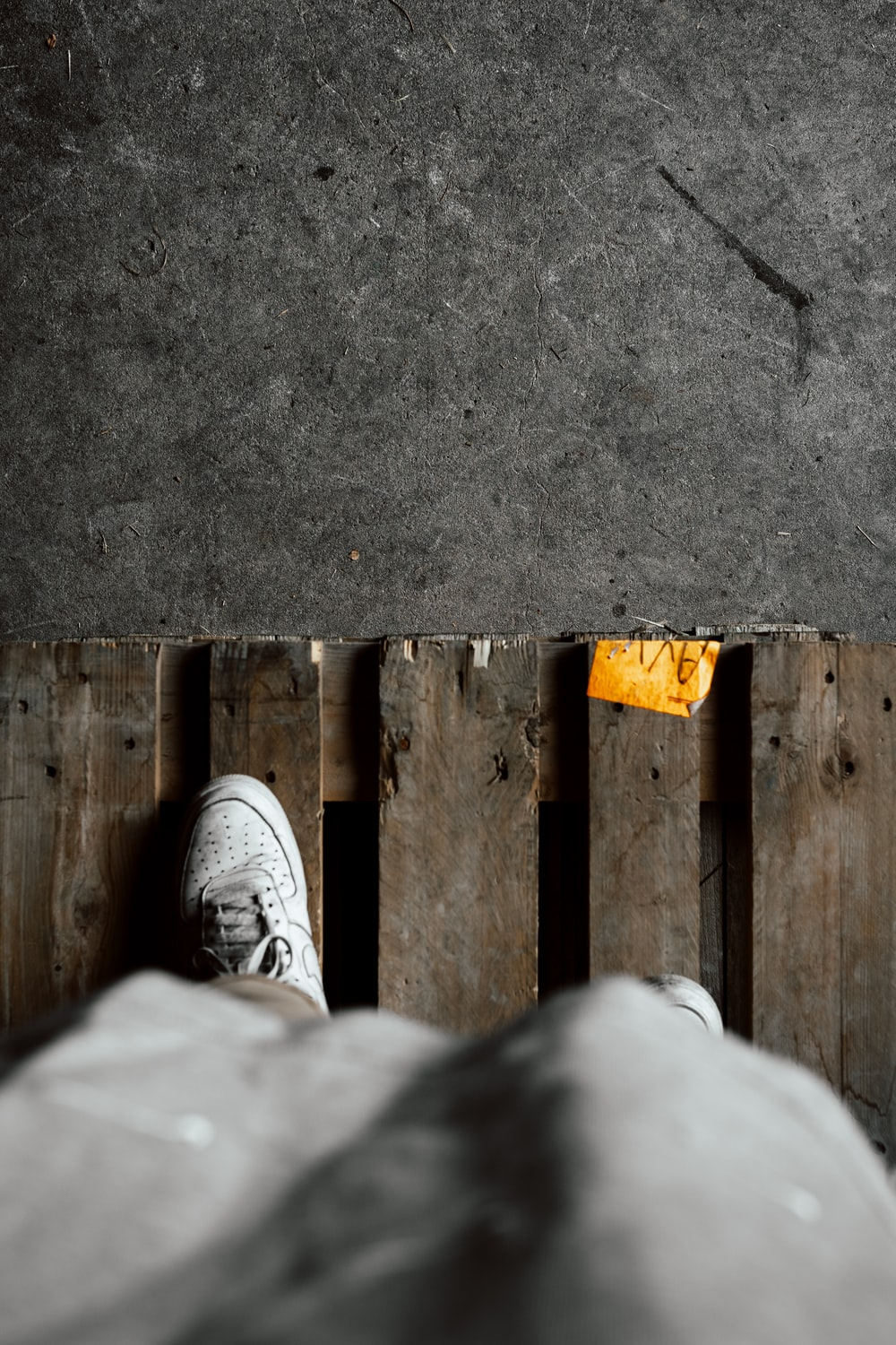 person in white pants and gray sneakers standing on gray concrete floor