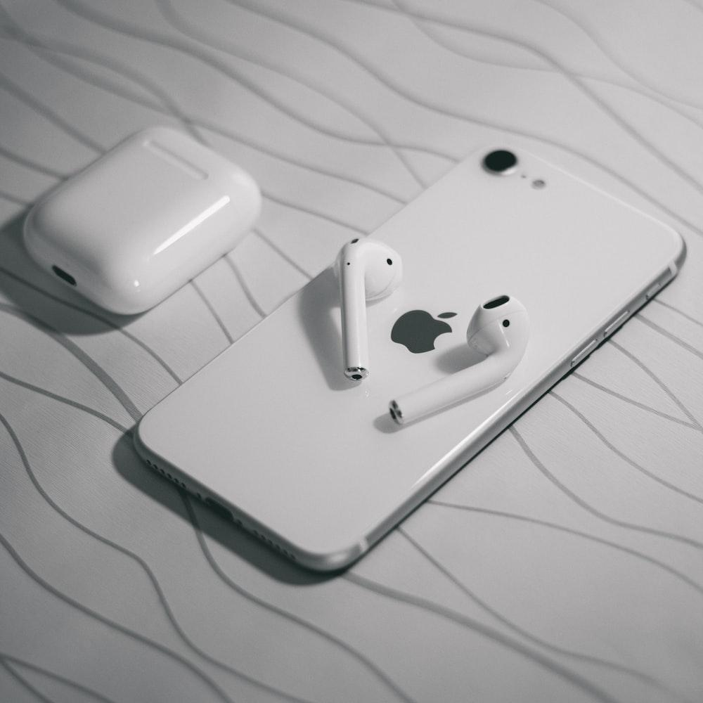 white apple earpods on white textile