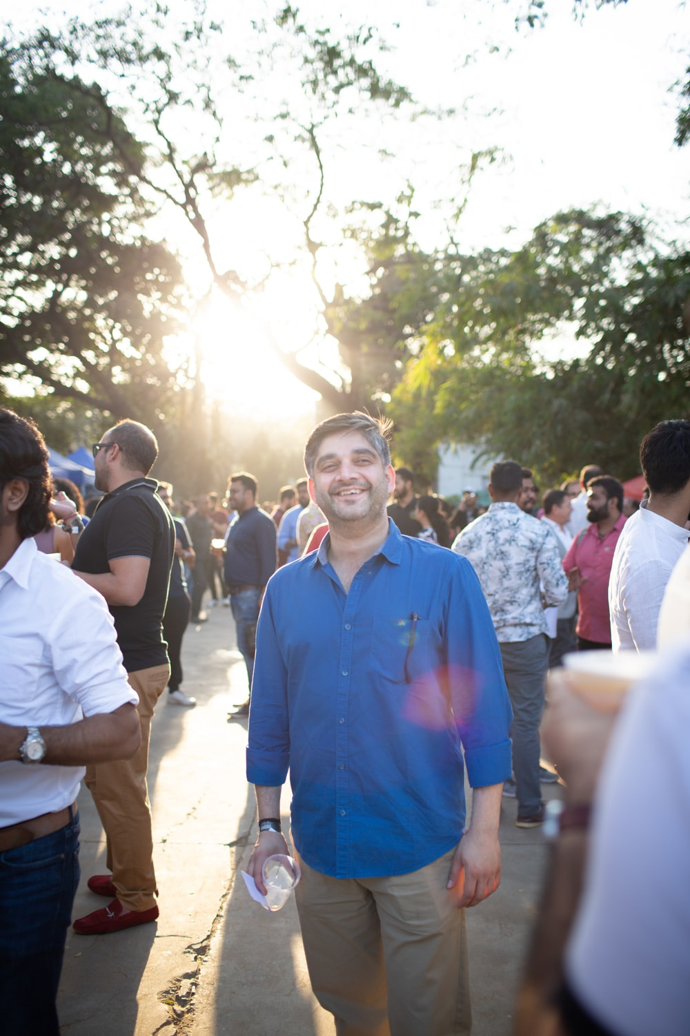 man in blue polo shirt standing near people during daytime