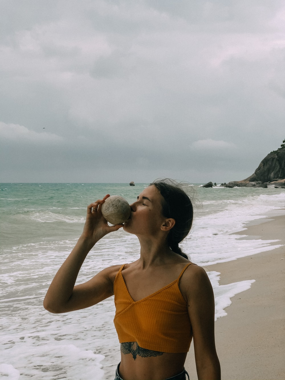 woman in orange tank top holding a gray stone near the sea during daytime
