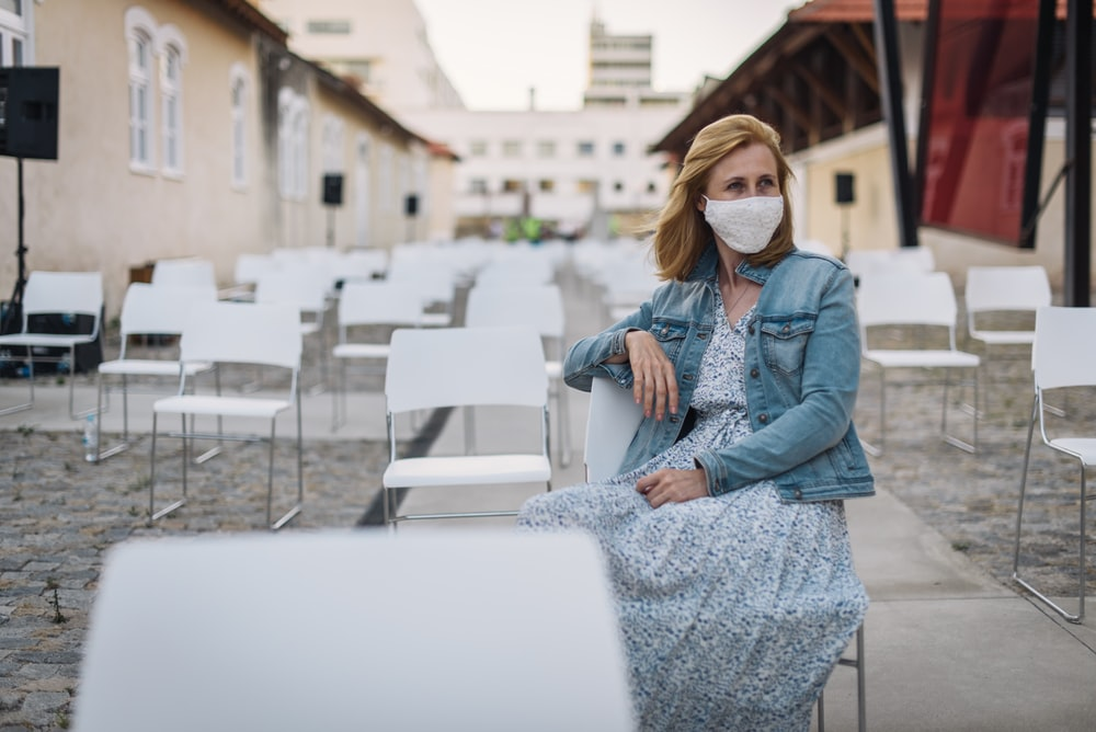 woman in blue denim jacket and white and black dress sitting on white concrete fence during