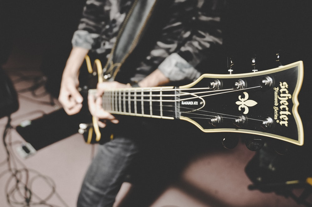 person playing electric guitar in black and white long sleeve shirt
