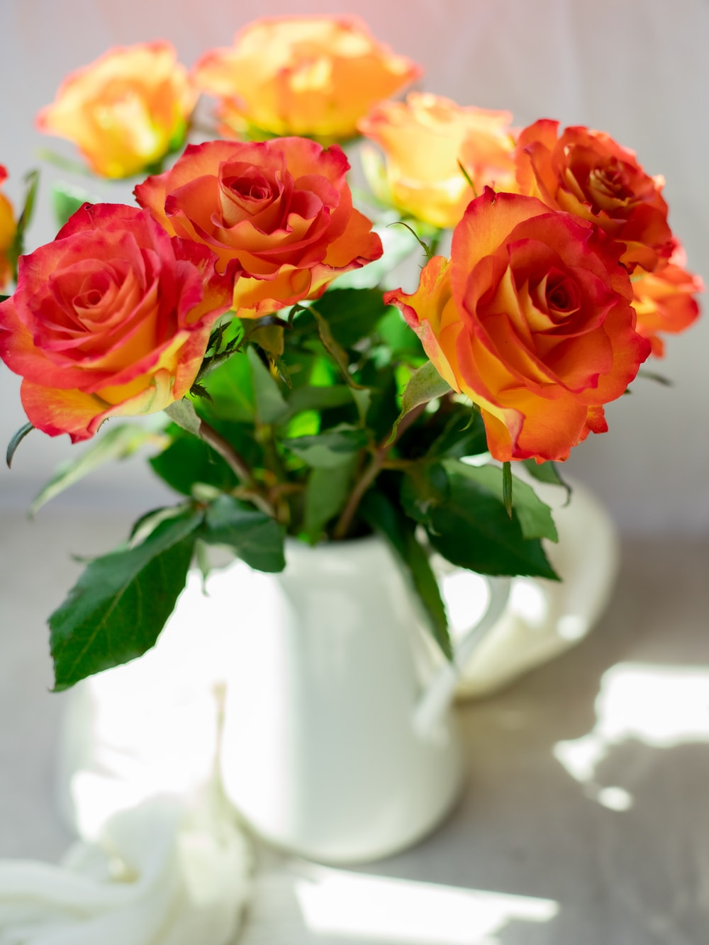 red and yellow roses in white ceramic vase