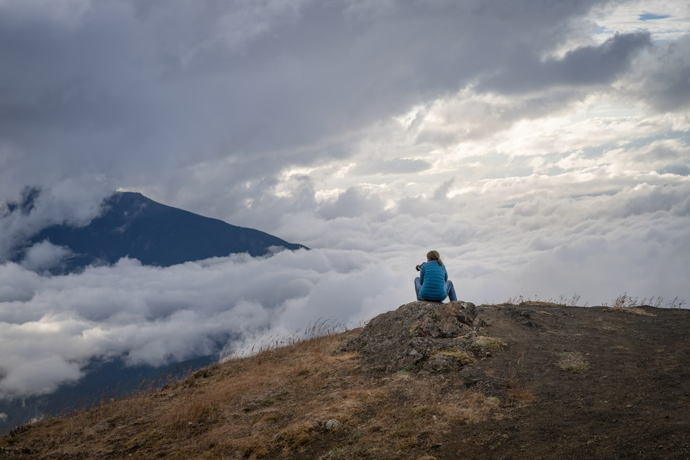 man in blue jacket sitting on brown rock mountain under white clouds during daytime