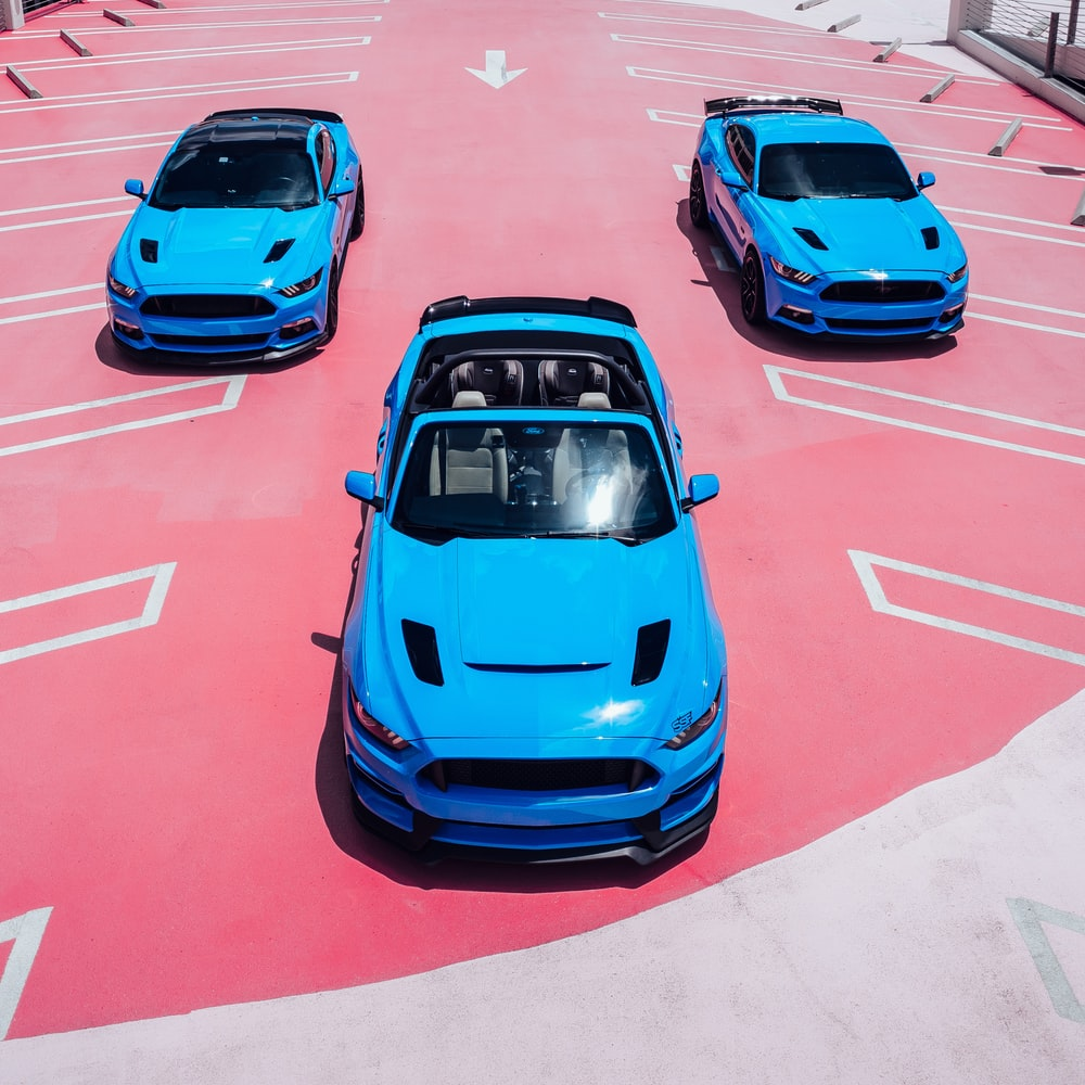 blue car on red and white road