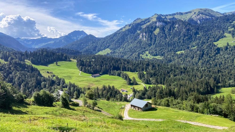 green grass field near green mountains under blue sky during daytime