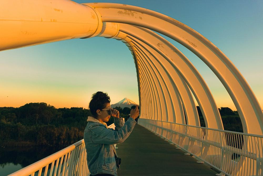 man in gray jacket standing on bridge during daytime