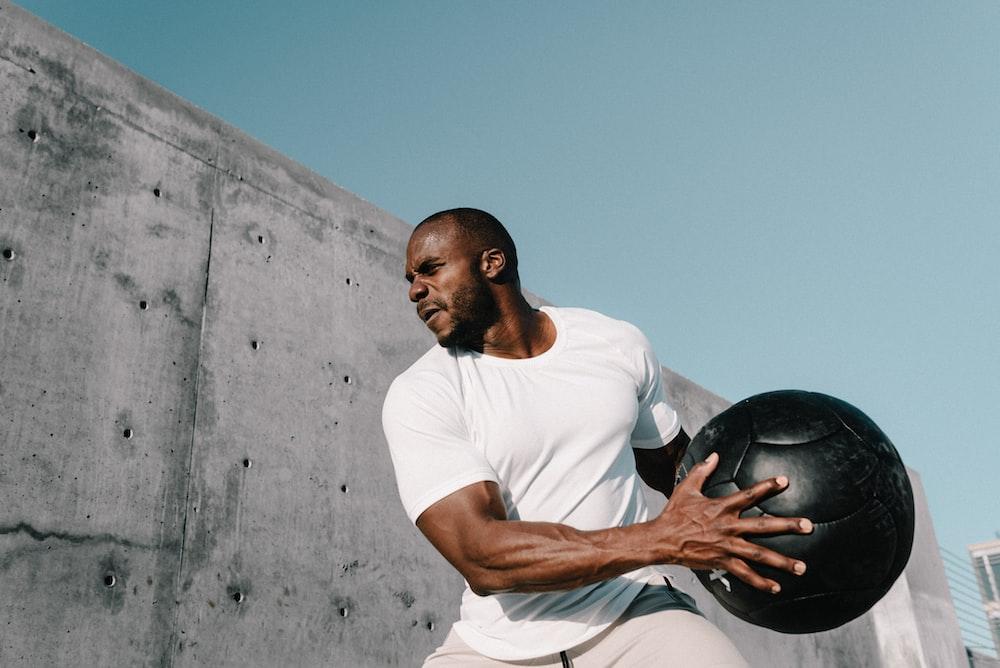 man in white crew neck t-shirt holding black ball