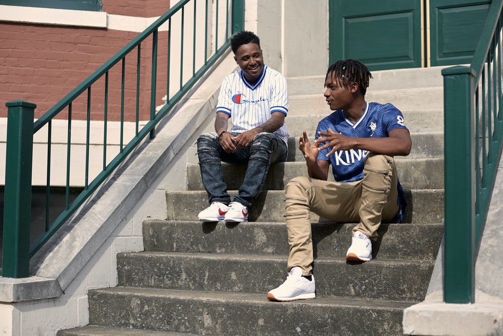 2 boys sitting on gray concrete stairs