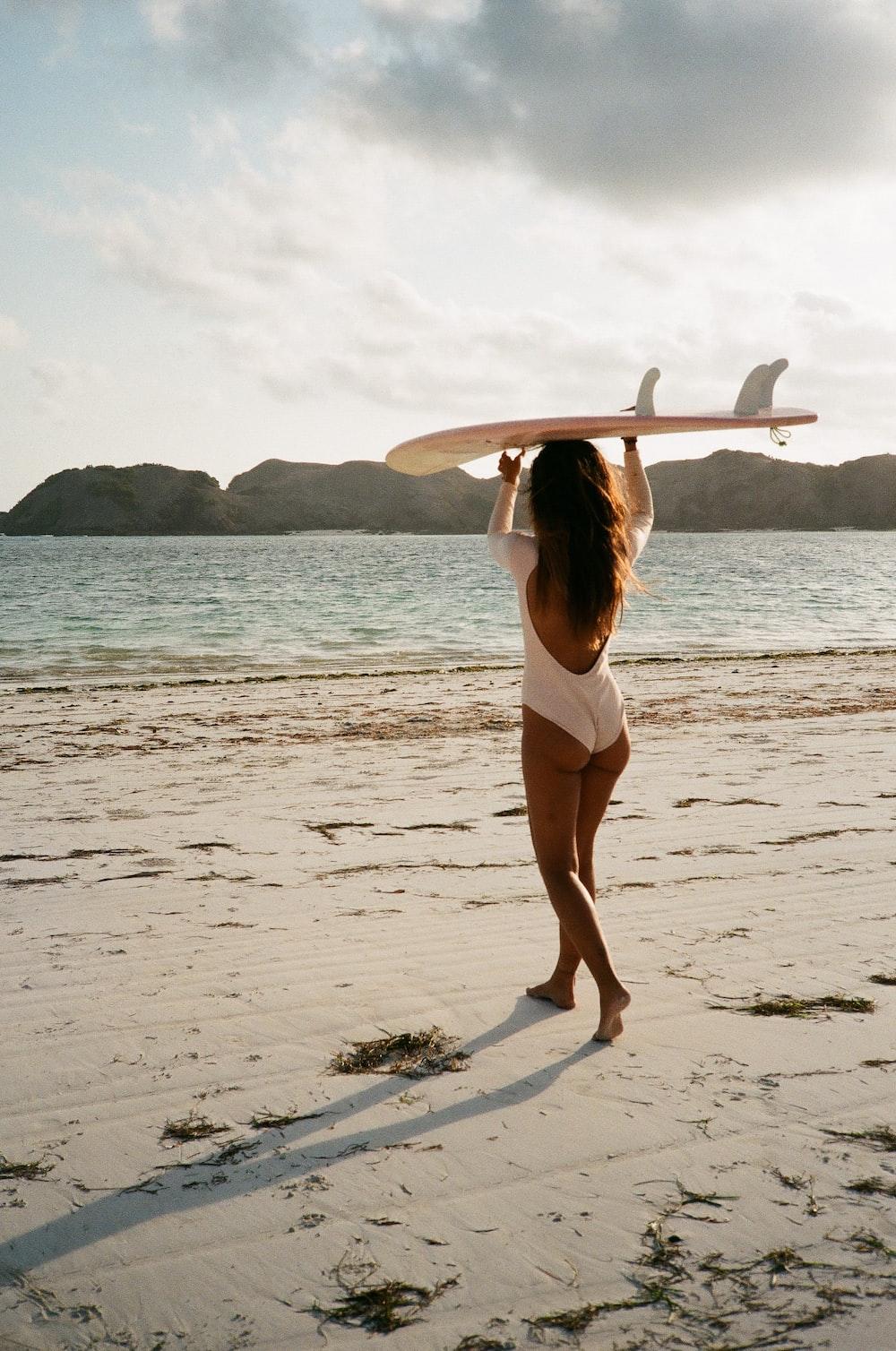 woman in white bikini holding white surfboard standing on beach during daytime