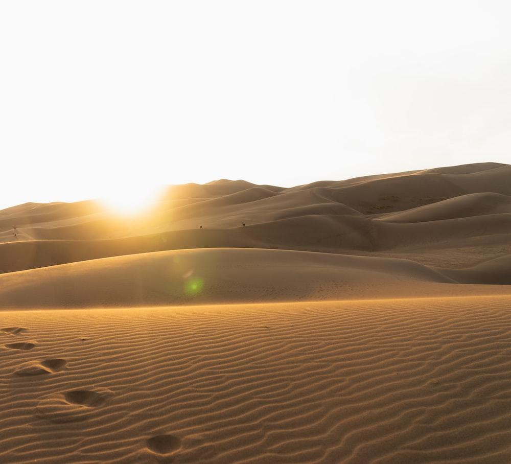 sand dunes under white sky during daytime
