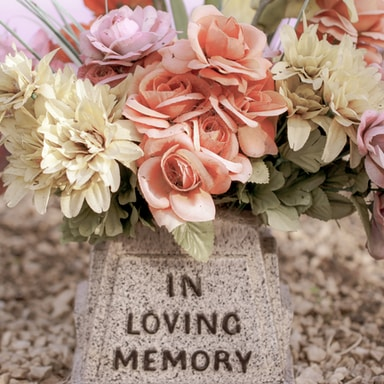 pink and white flowers on gray concrete tomb