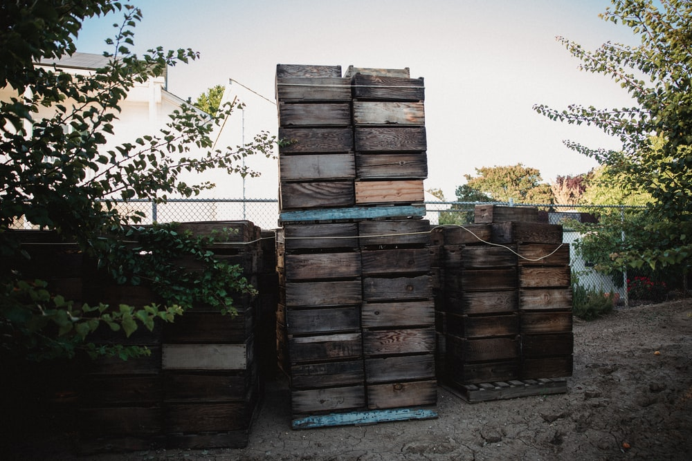 brown wooden crates near green plants during daytime