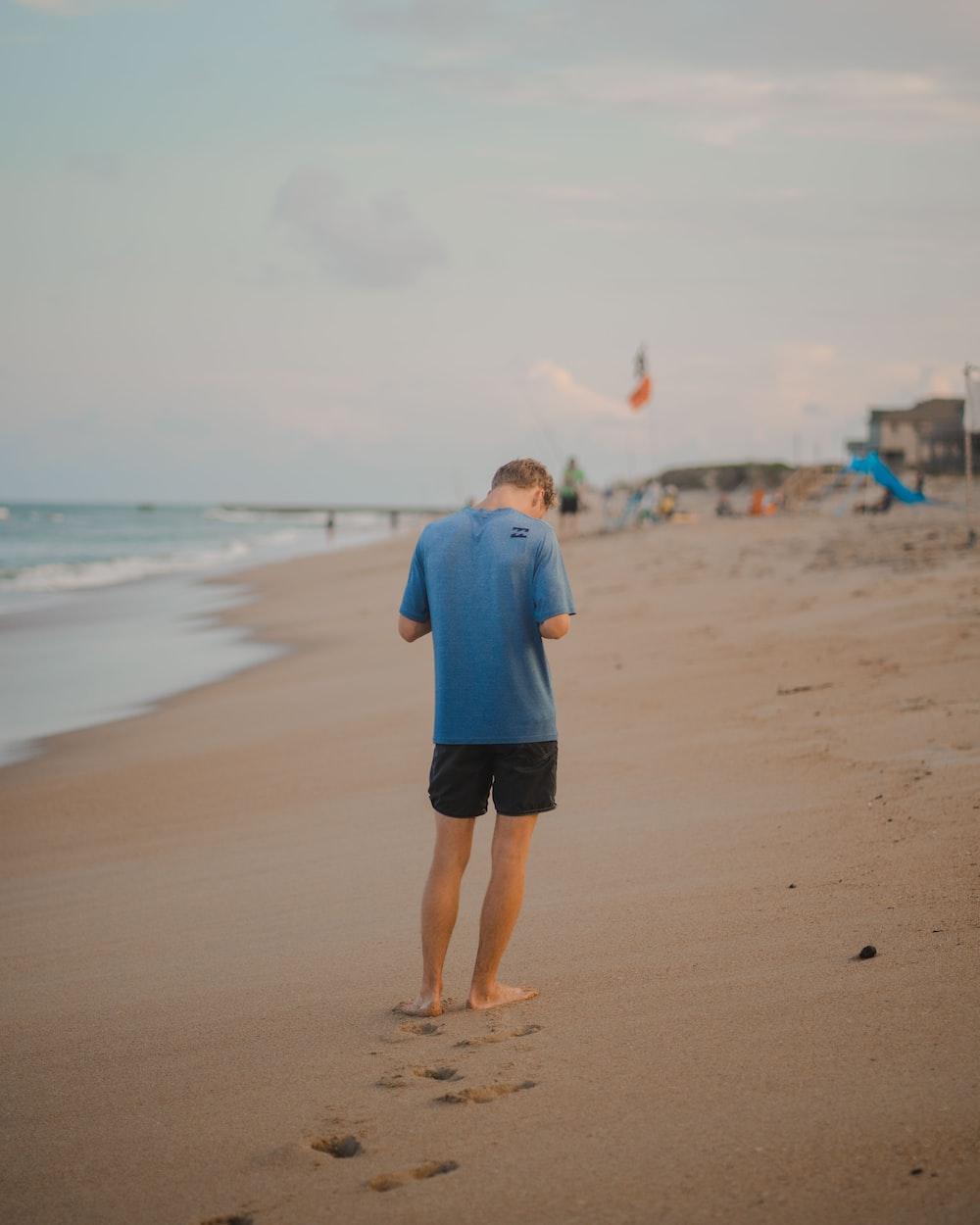 man in blue dress shirt and black shorts walking on beach during daytime