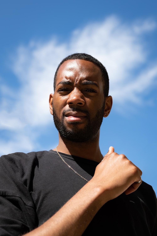man in black crew neck shirt wearing white earbuds