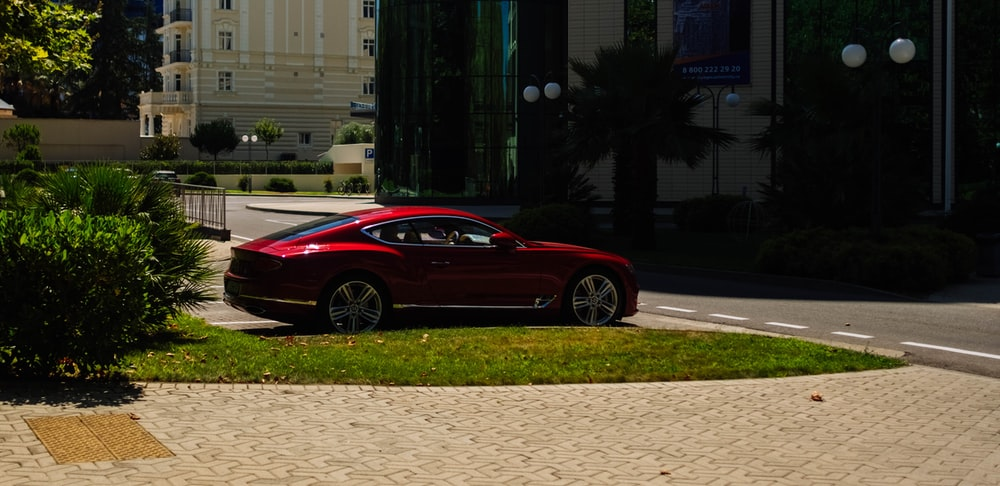 red coupe parked on sidewalk during daytime