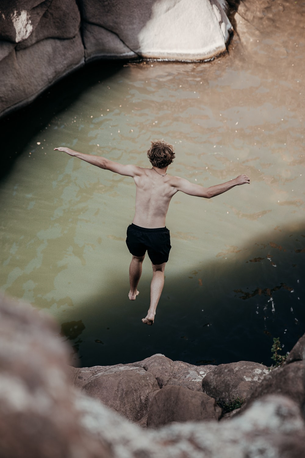 man in black shorts standing on water during daytime