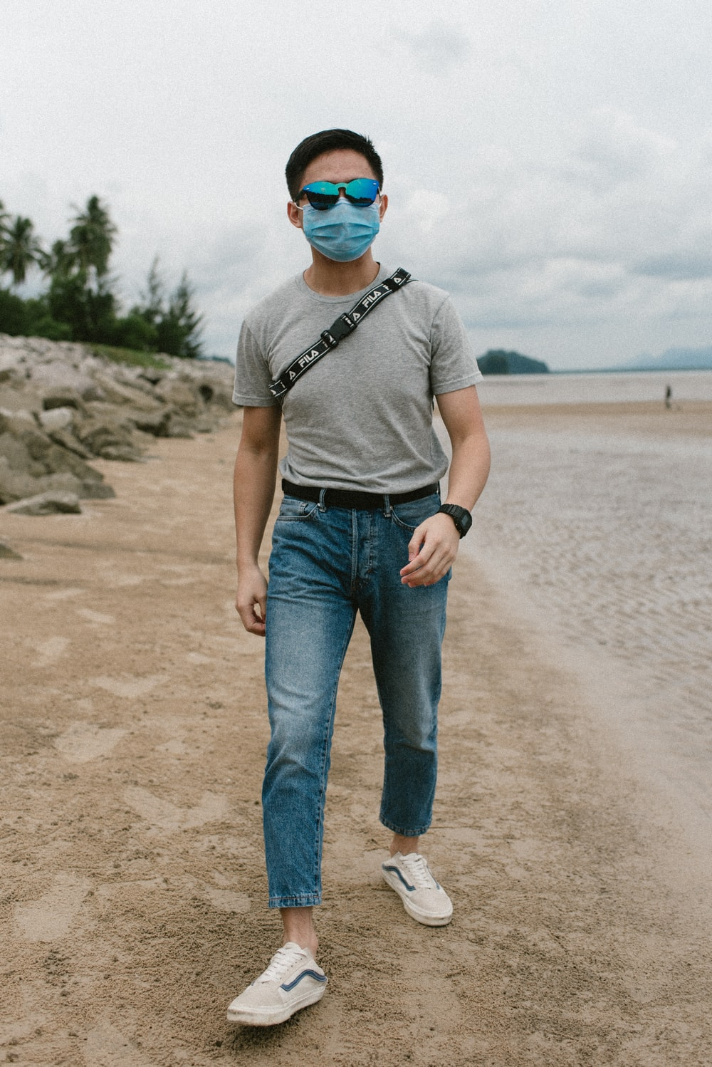 man in gray crew neck t-shirt and blue denim jeans standing on beach shore during