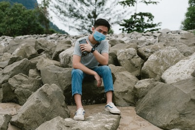 Kuching boy in black t-shirt and blue denim shorts sitting on rock during daytime