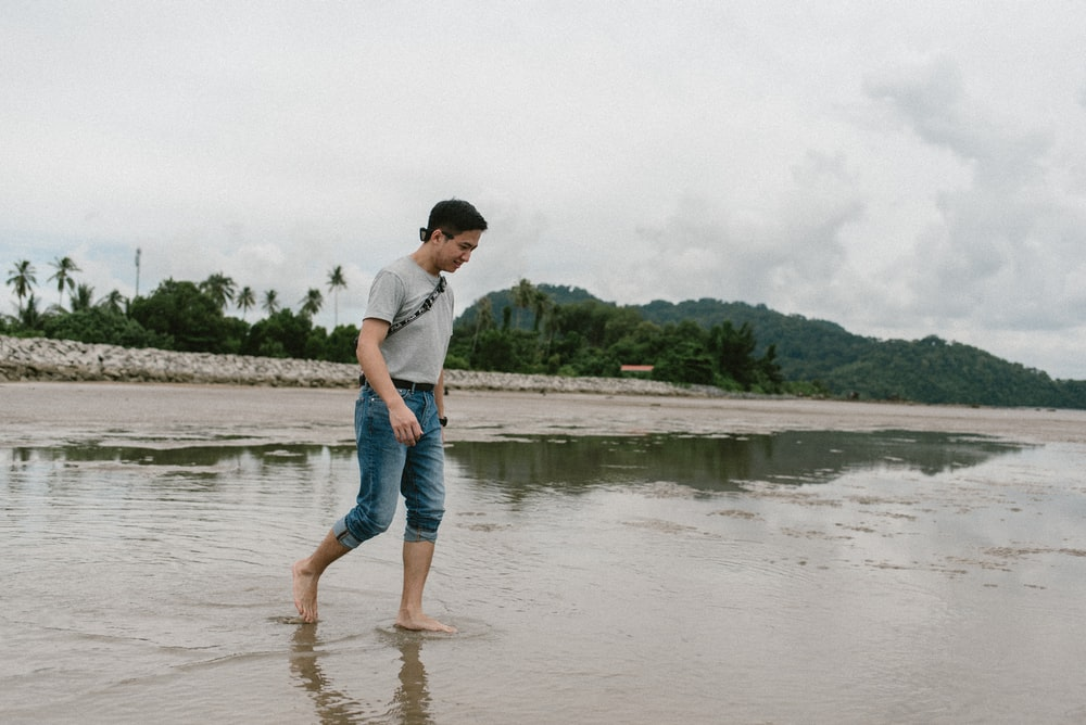 man in white t-shirt and blue denim shorts standing on water during daytime