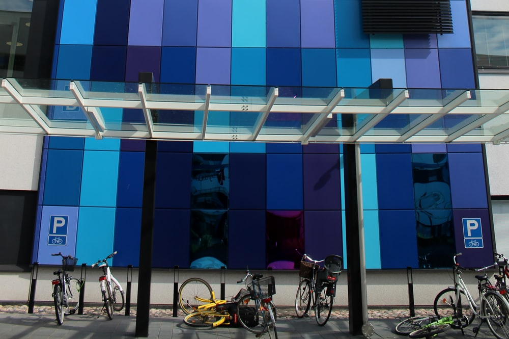 white and black city bikes parked beside blue and white building during daytime