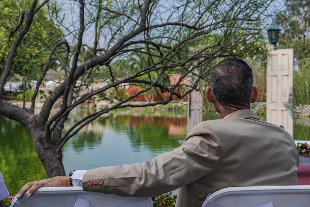 man in brown jacket sitting on bench near lake during daytime
