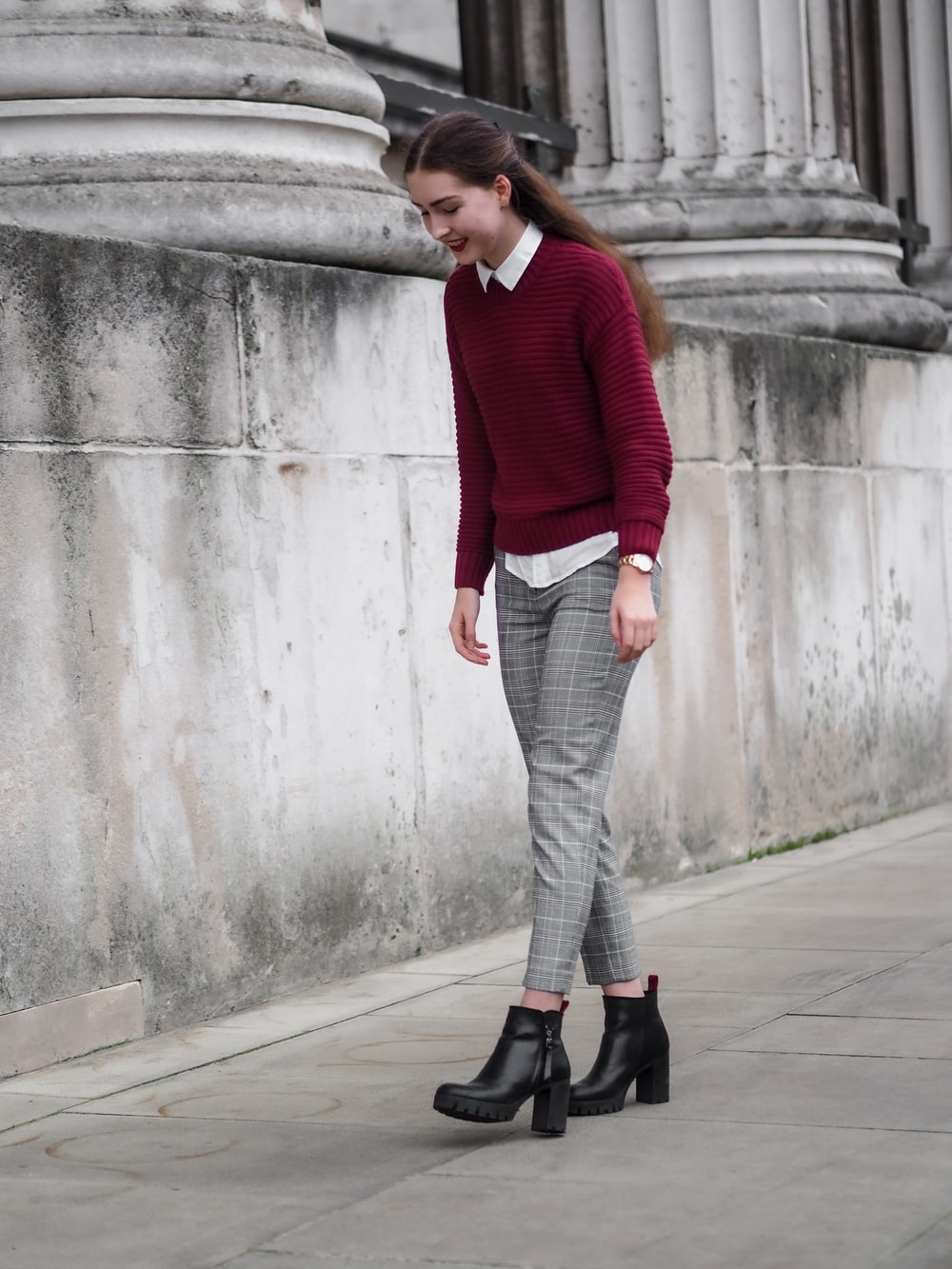 woman in red sweater and gray pants standing on sidewalk during daytime
