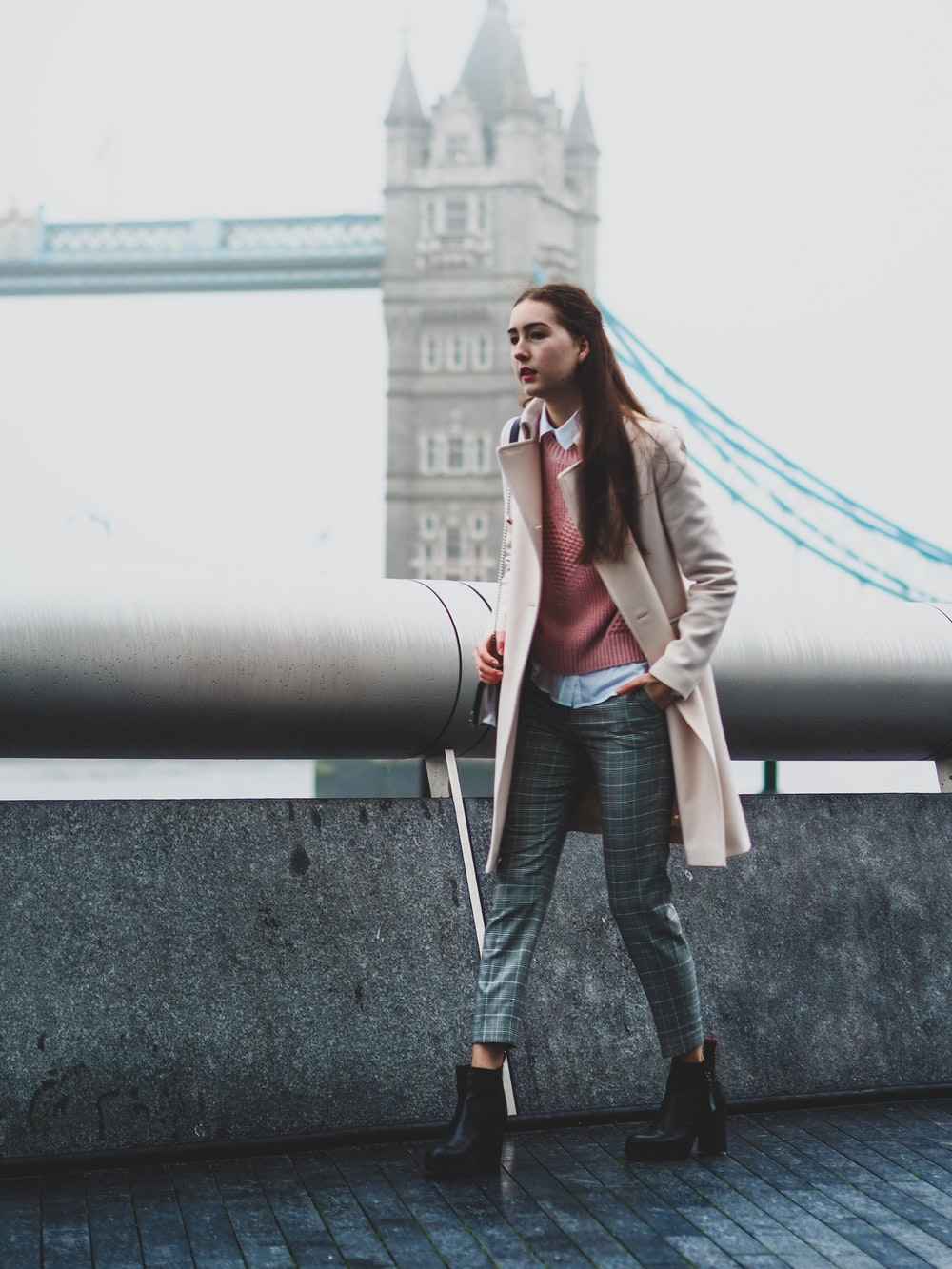 woman in gray blazer and black pants standing beside gray metal pipe