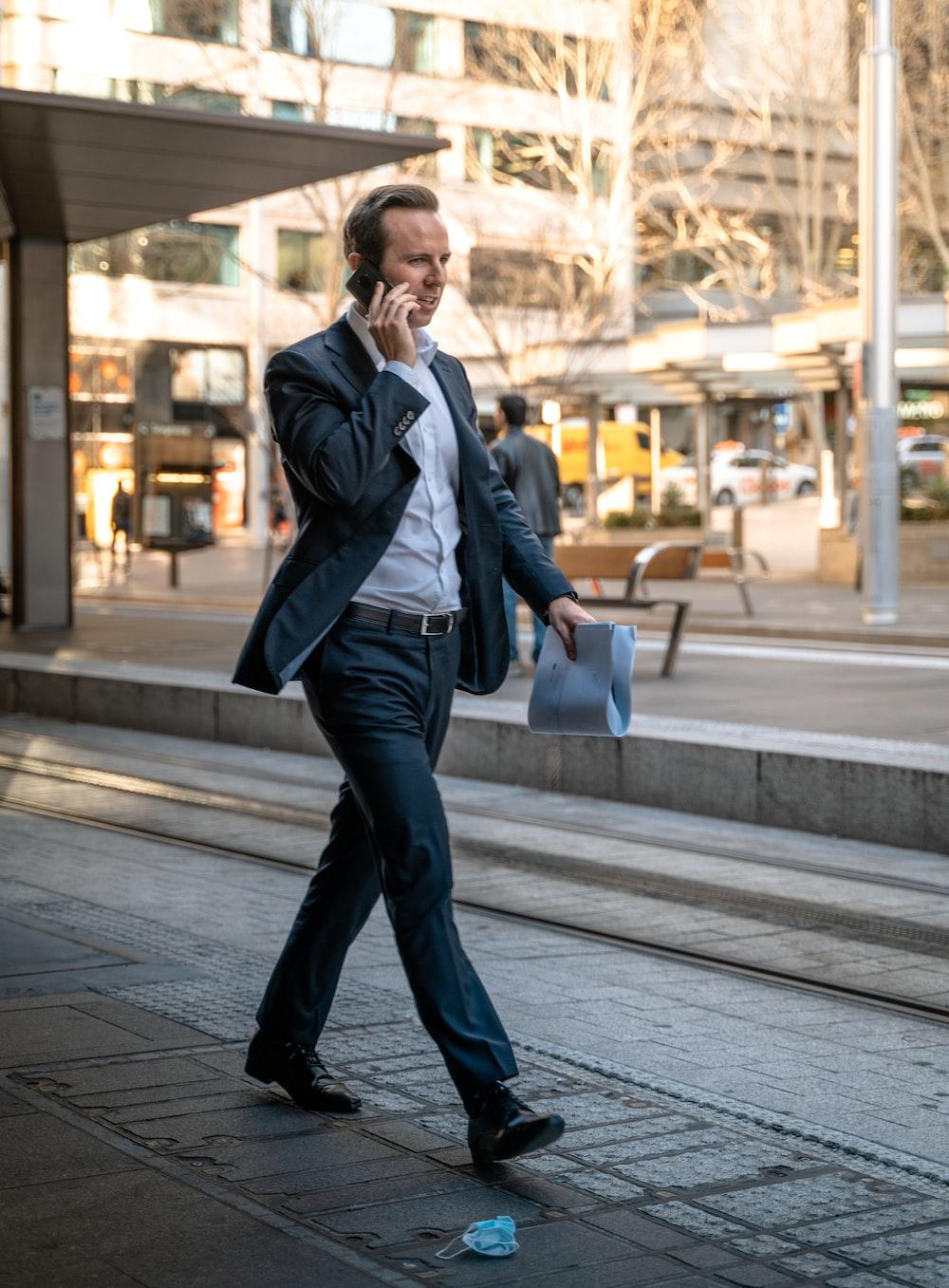 man in black leather jacket and blue denim jeans standing on sidewalk during daytime