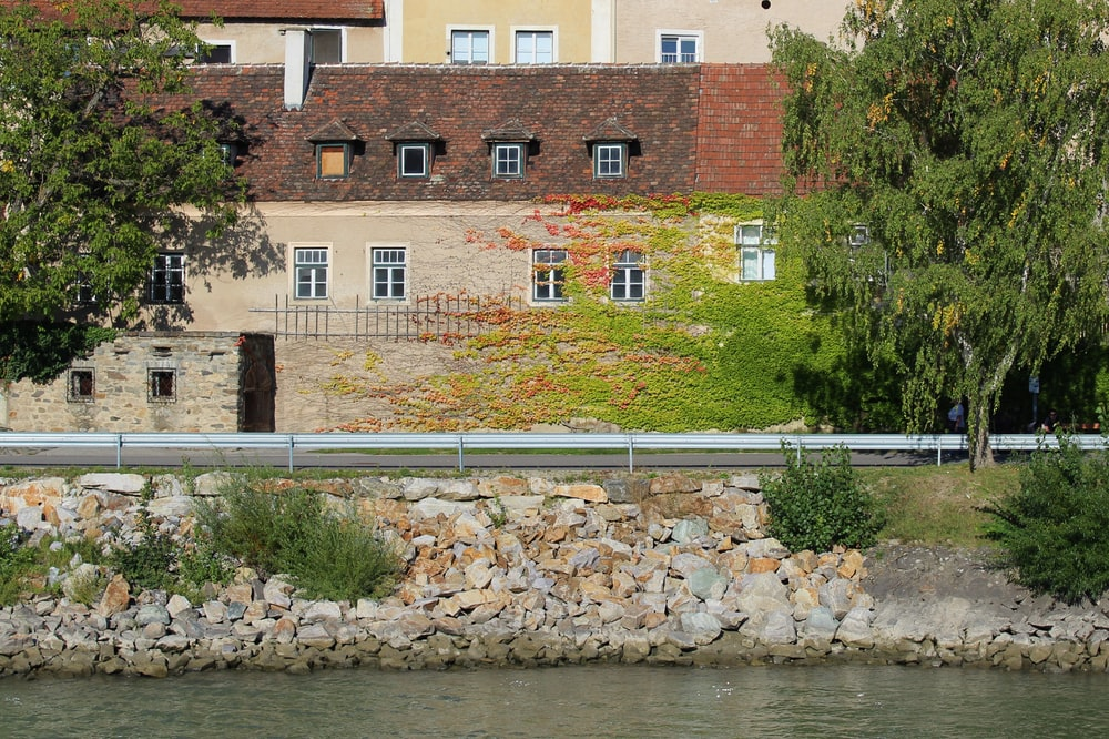 brown concrete building beside river during daytime