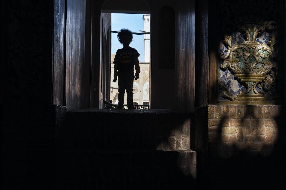 man in black jacket standing on window