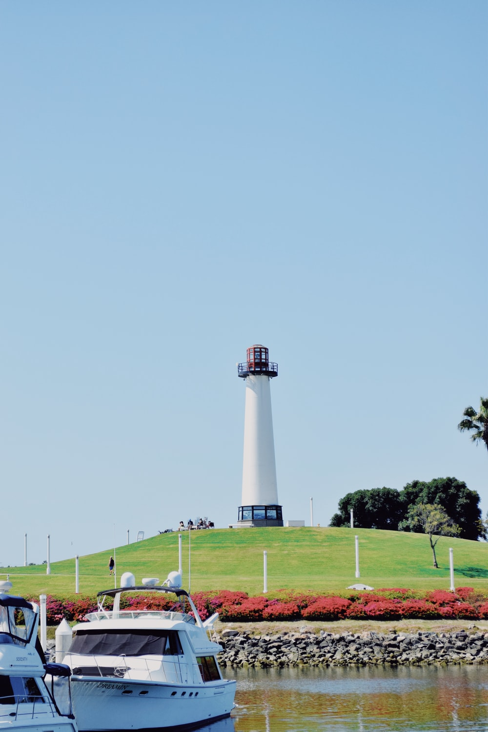 white and black lighthouse on green grass field under blue sky during daytime