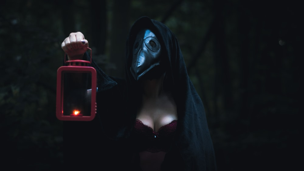 woman in black hoodie holding red and black smartphone