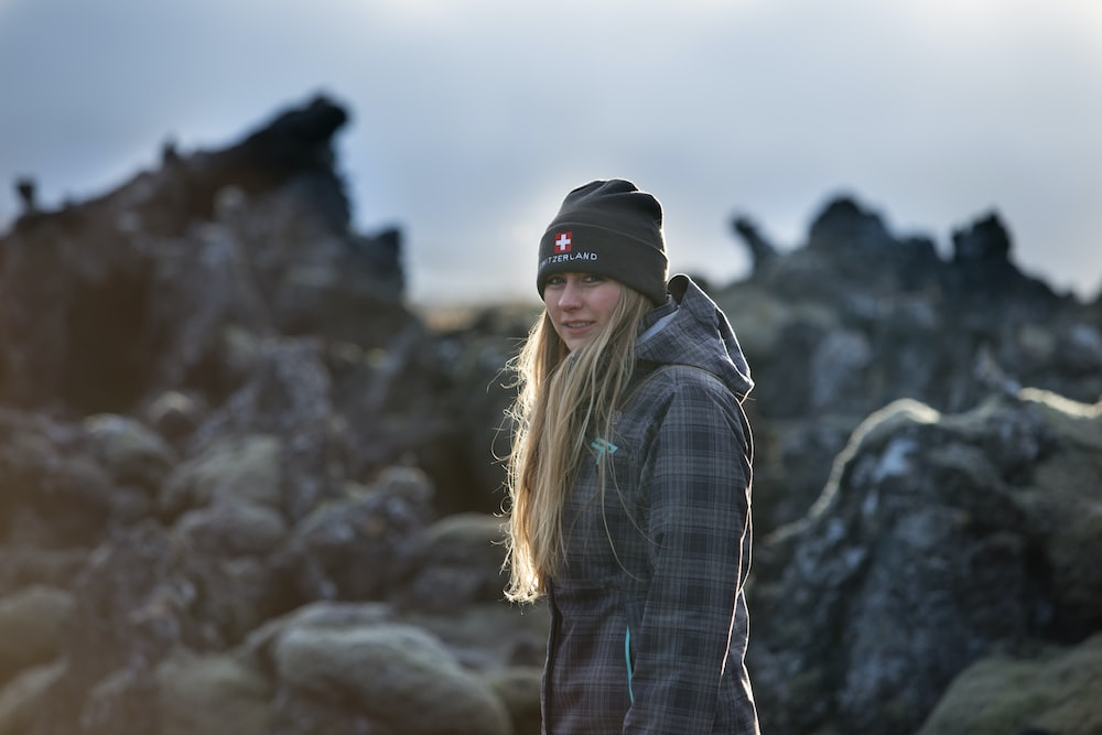 woman in black and white plaid dress shirt and black cap standing on rock formation during