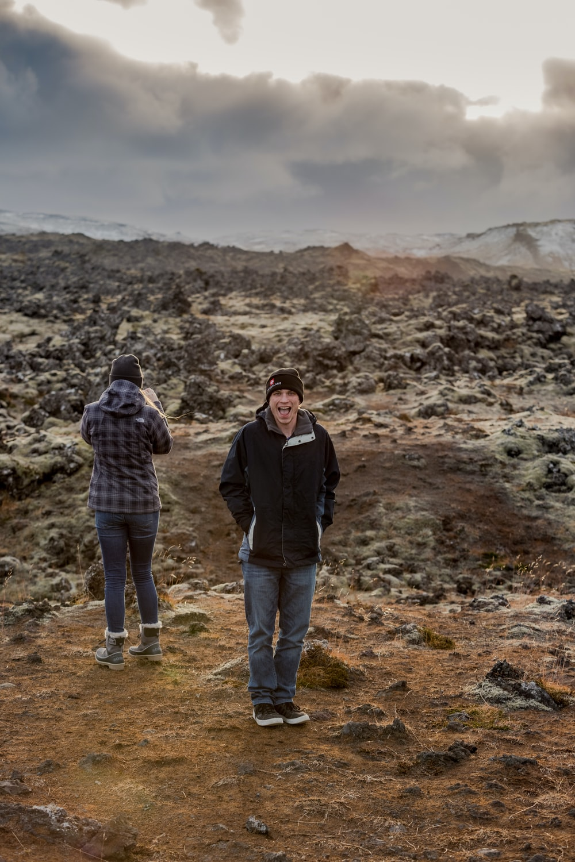 man in black jacket standing beside woman in brown jacket