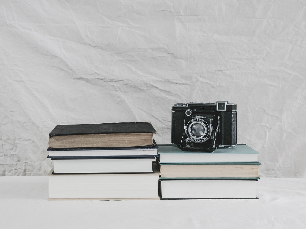 black and silver camera on brown book