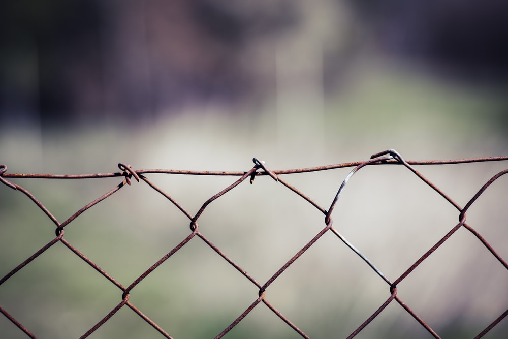 gray metal fence with barbwire