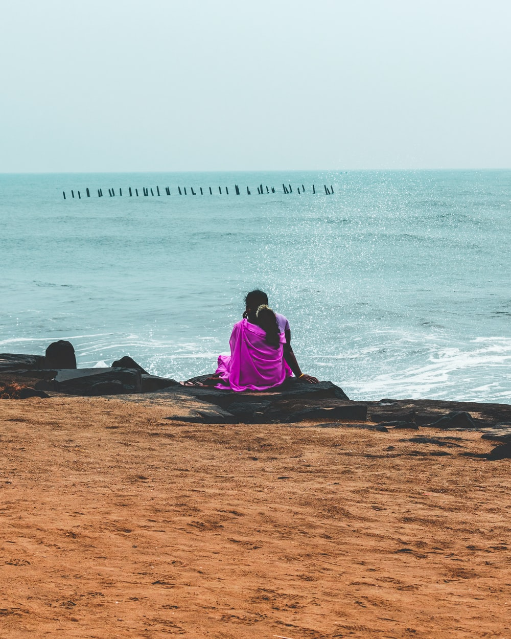 woman in purple long sleeve shirt sitting on brown sand near body of water during daytime