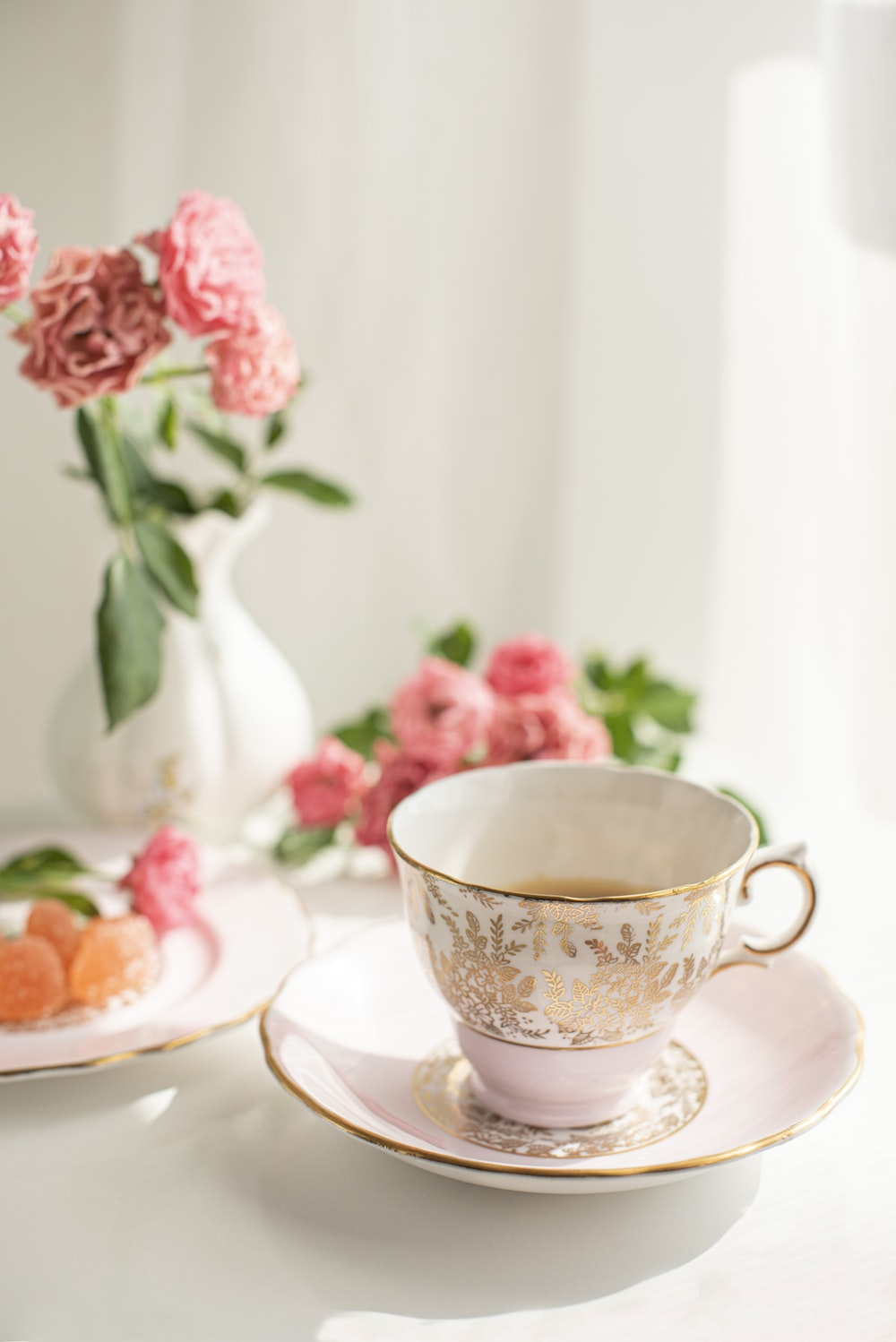 white and pink floral ceramic teacup on saucer