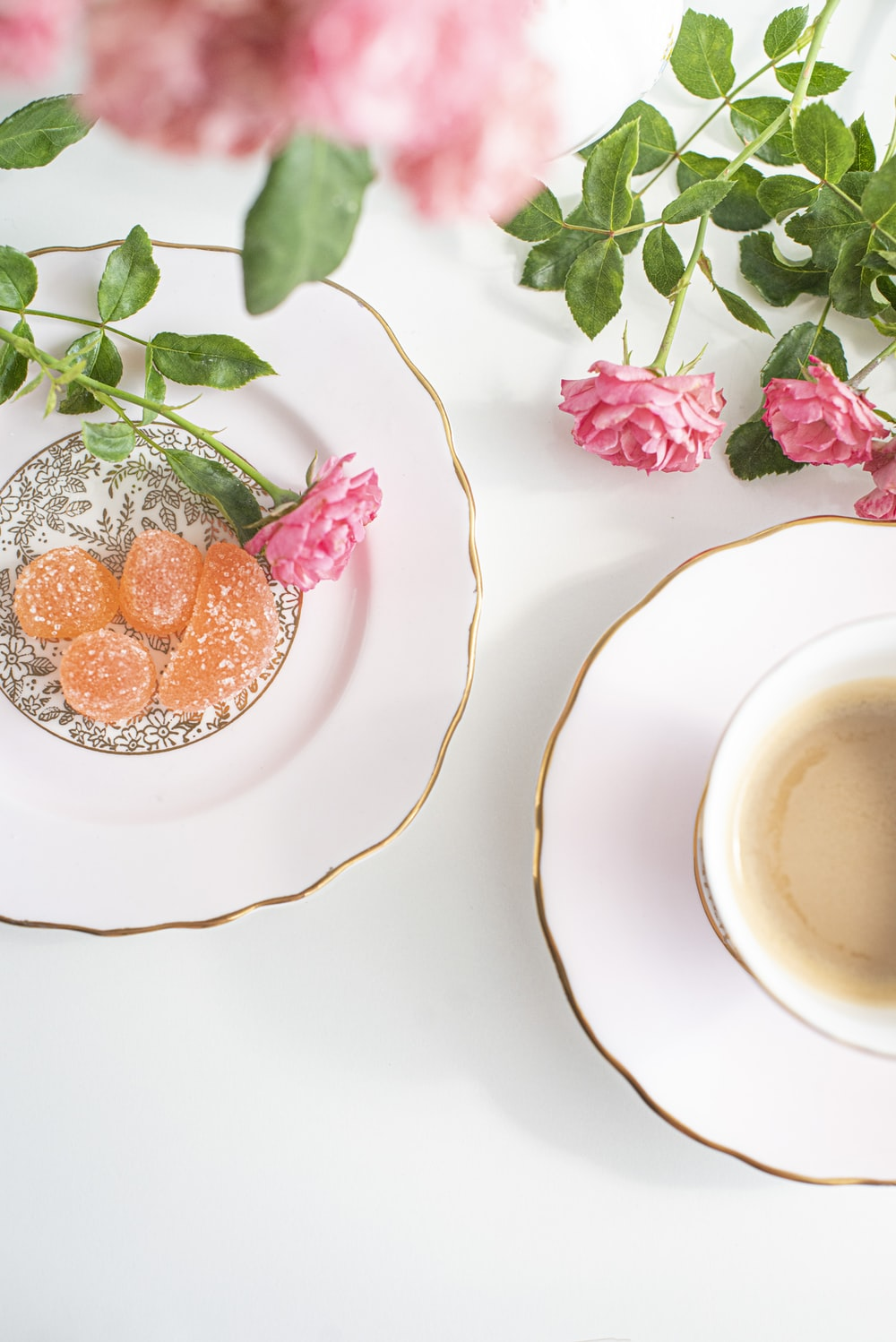 white ceramic cup with saucer beside pink flowers