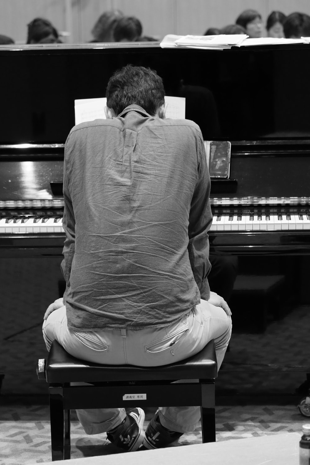 man in long sleeve shirt sitting on piano