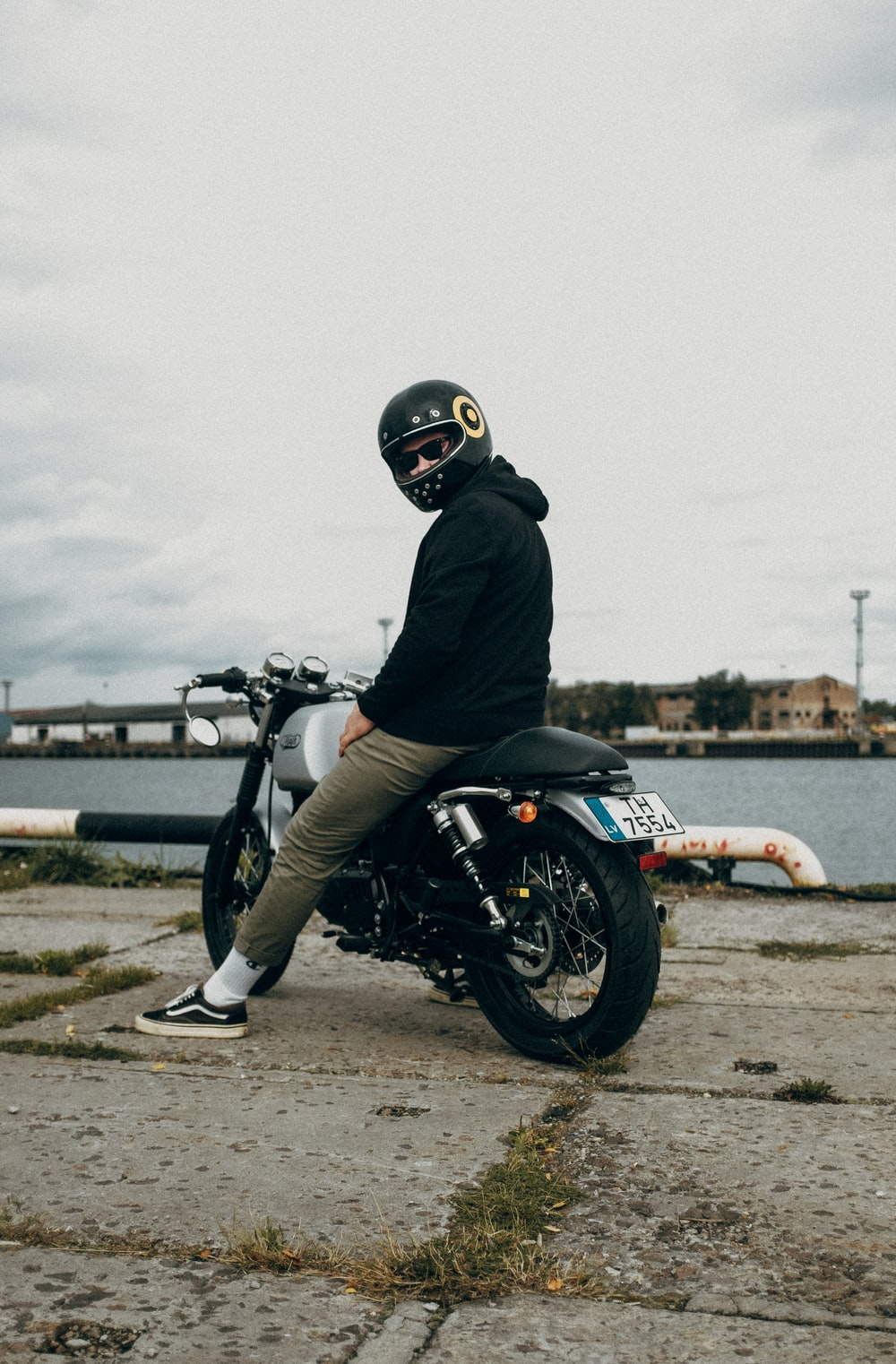 man in black jacket riding on white and black sports bike
