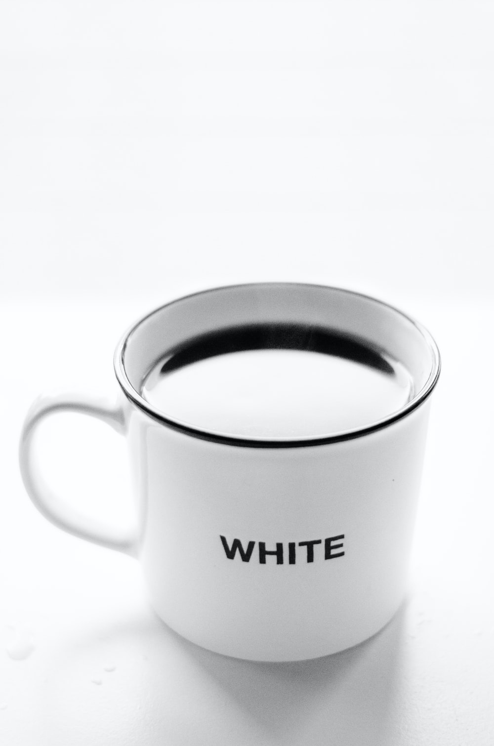 white and black ceramic mug with coffee